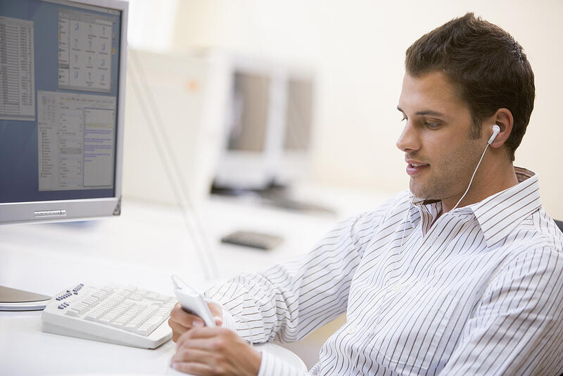 Learning People   Finance project manager looking at phone in office with headphones