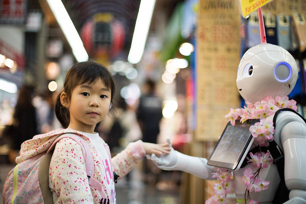 Small child holding hands with a robot