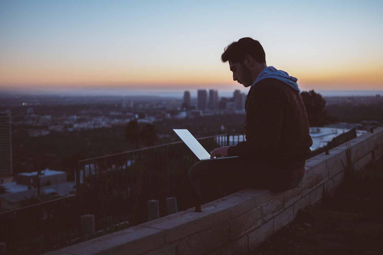 man-sat-on-wall-on-laptop.jpg