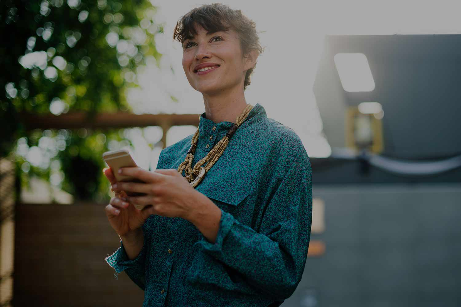 woman-smiling-with-phone-in-hand