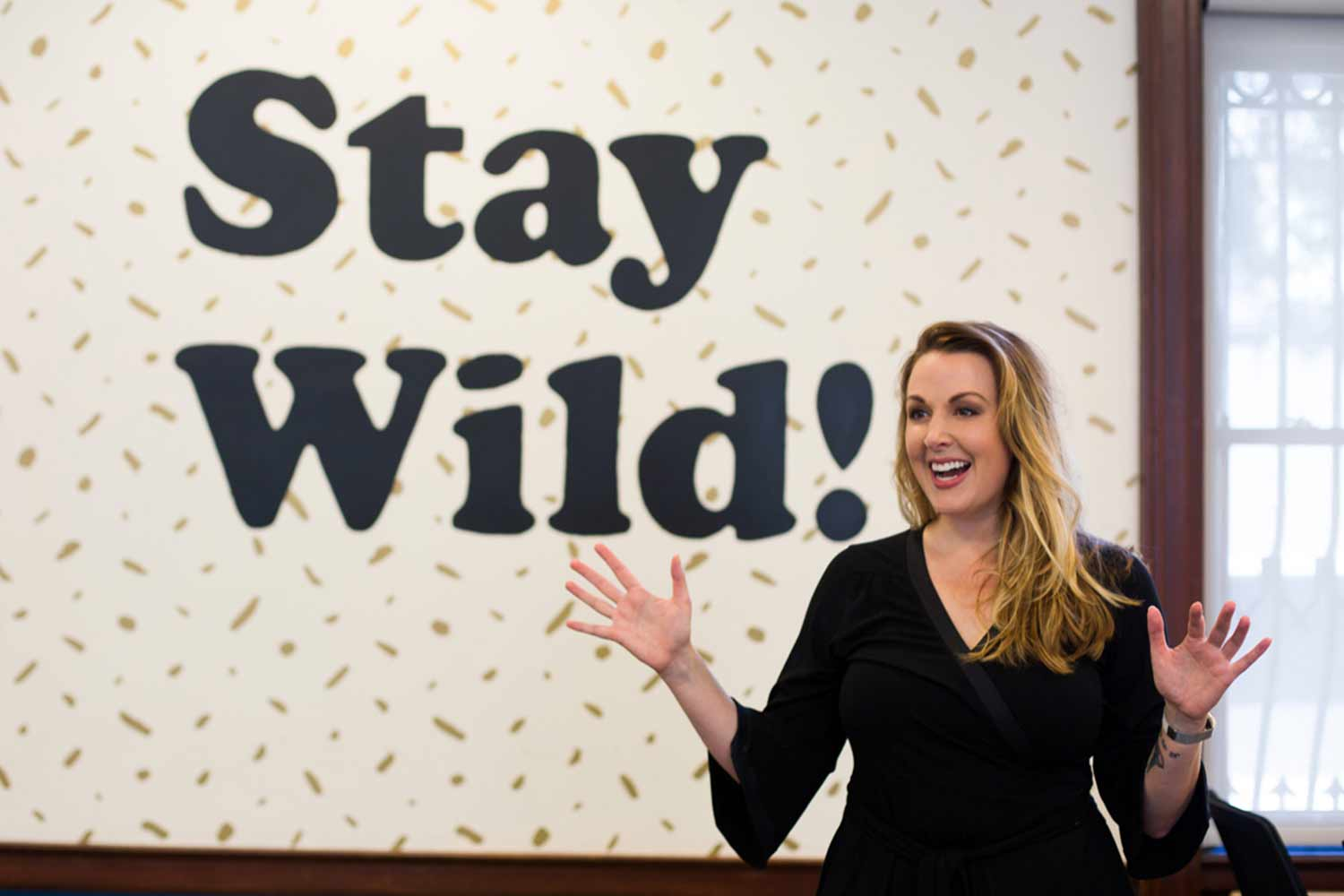 woman in front of wall that says stay wild